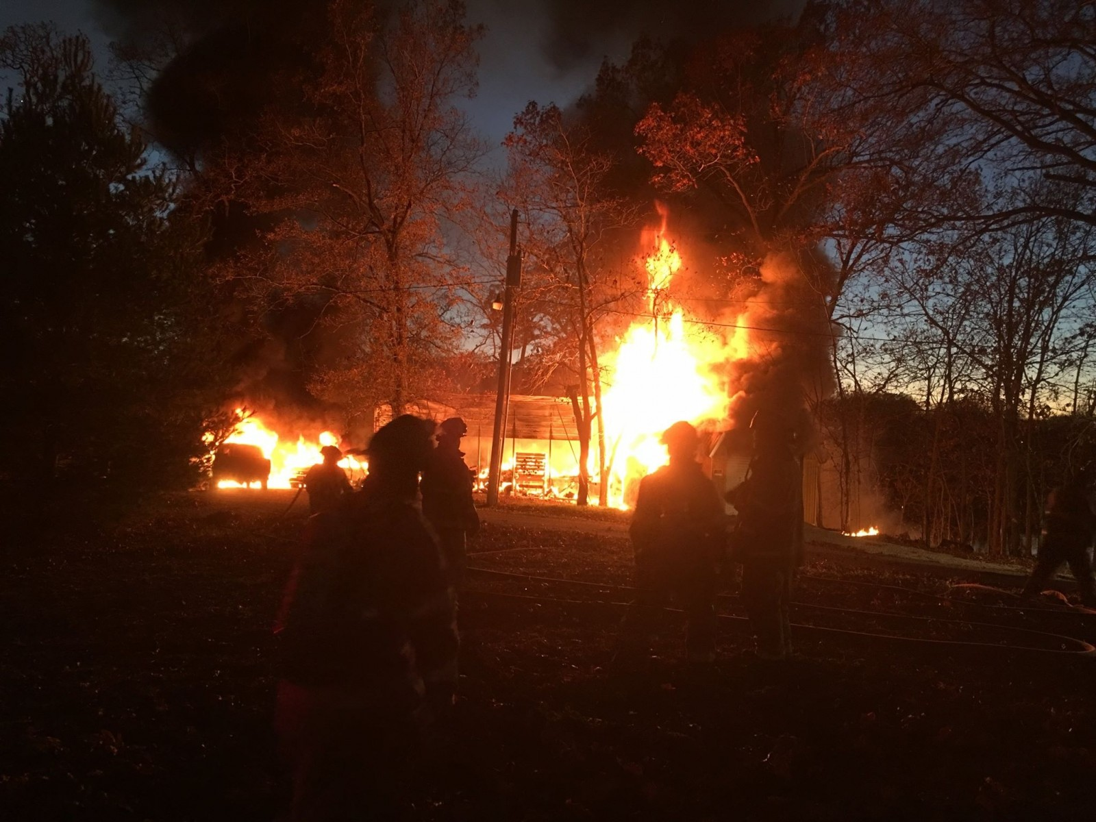 Firefighters attempt to contain the blaze at a Pana Lake residence on Sunday. Photo Courtesy of a Pana Police Department Press Release.